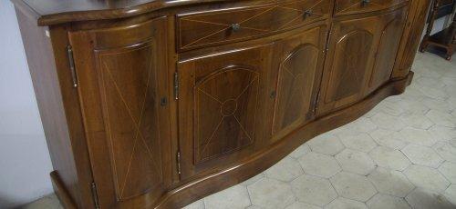 Moble menjador corbat, fabricat en fusta massissa de noguer. Incrustacions de marqueteria de boix a les portes i calaixos.