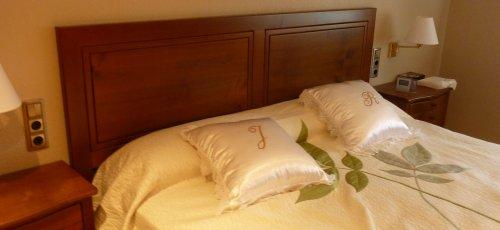Dormitori amb capçal plafonat i tauletes ventrudes amb calaixos. Fabricat en fusta de cirerer massís.