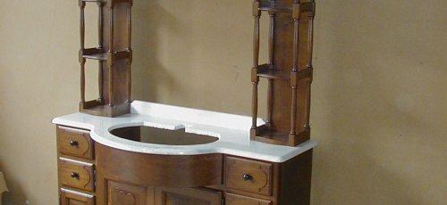 Moble de bany amb portes plafonades, calaixos, sobre de marbre i columnetes tornejades. Flors tallades a mà. Fabricat en fusta de roure massís.