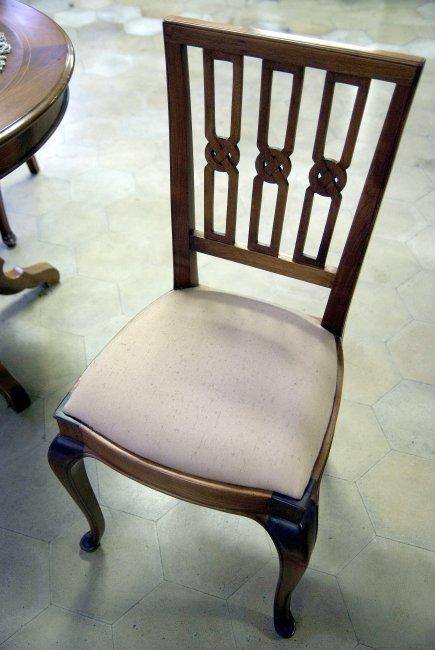 Cadira de fusta amb plafons tallats a mà, seient entapissat i respatller inclinat. Fabricat en fusta de noguer