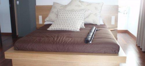 Cama habitación. Mesitas integradas al cabezal y colchón enmarcado en madera. Fabricado en madera de roble macizo.