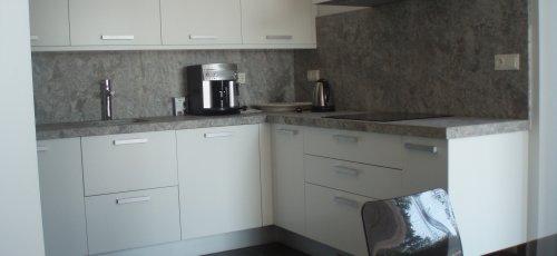 Cocina de melanina blanca. Sobre y paredes de mármol .