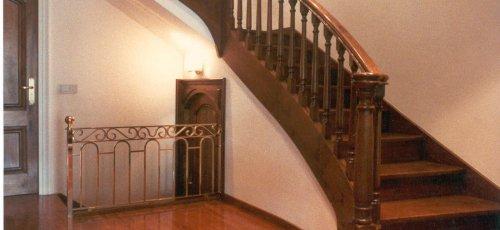 Escalera curva con balaustres torneados y escalones de madera. Fabricada en madera  de nogal macizo.