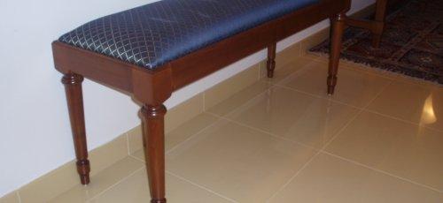 Banqueta tapizada con patas torneadas. Fabricada en madera de cerezo mcizo.
