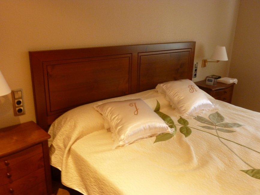 Dormitorio con cabezal plafonado y mesitas ventrudas con cajones. Fabricado en madera de cerezo macizo.