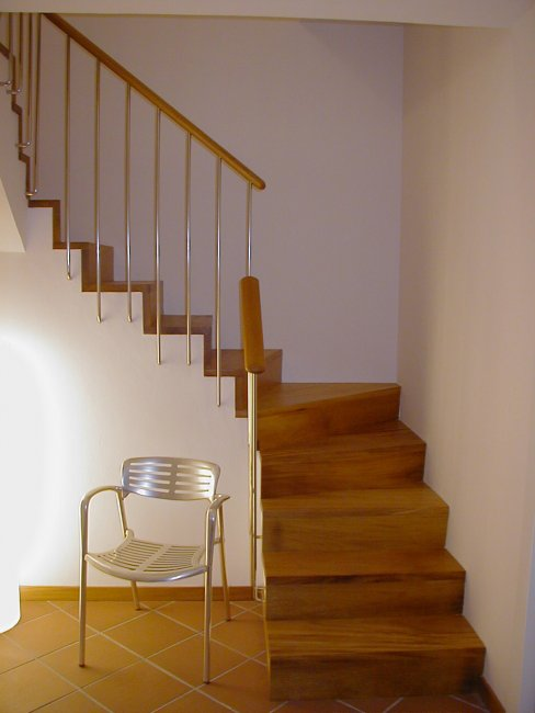 Escalera forrada en madera de iroco. Barandilla en inox y madera.