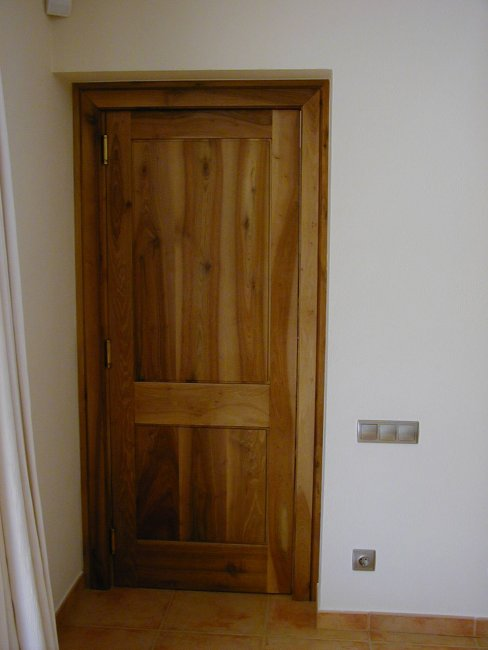 Puerta maciza de dos plafones en madera de nogal.
